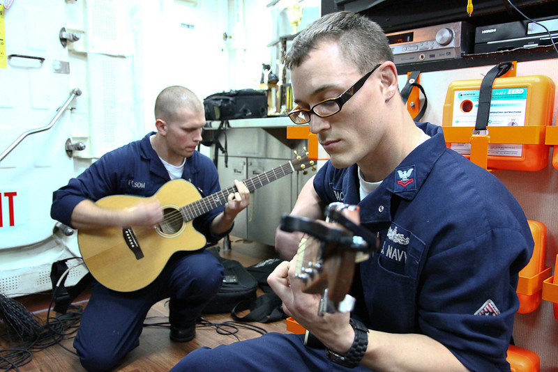 Sailors warm up their guitars for the Mustin Idol competition.