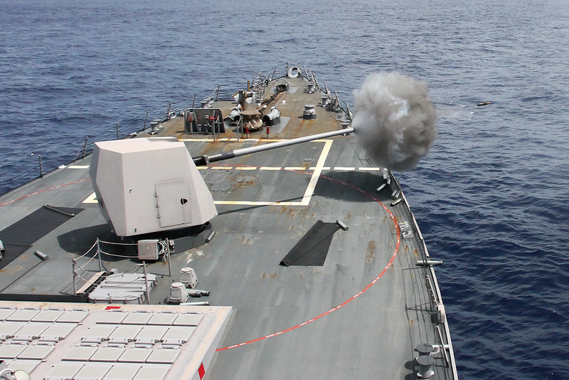 USS Mustin fires her 5 inch gun mount while conducting Naval Surface Fire Support (NSFS) qualifications.  The ship fired at land targets practice supporting an amphibious invasion.
