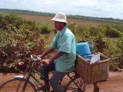 Cambodian man riding bicycle in countryside