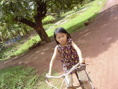 Young Cambodian girl gives intense look on bicycle