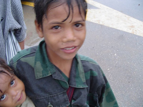Young Cambodian boys begging for money in rain.