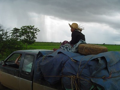 Cambodian woman riding on top of truck with rain storm in background