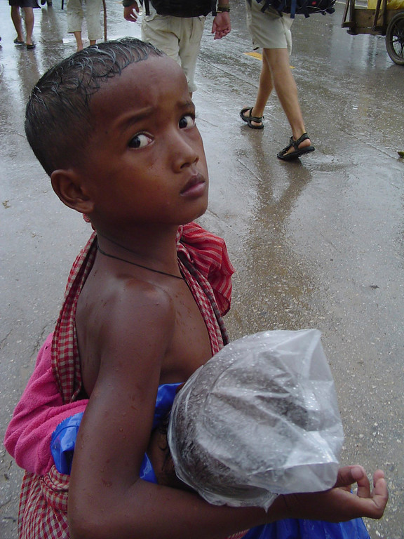 Young Cambodian boy holding brother with palstic bag on head.