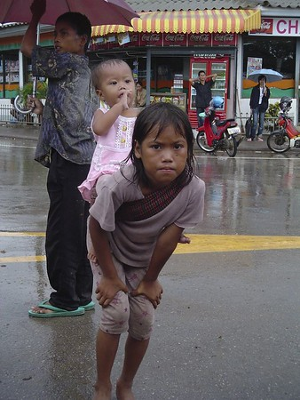 Young Cambodian girl with baby sister on back begging for money in rain.