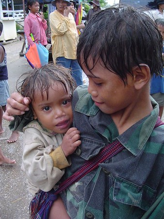 Young Cambodian boy holding younger brother smiling.