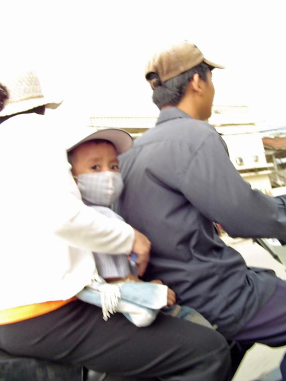 Cambodian boys wears face mask on motor bike in Phnom Phen