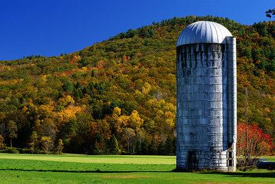A monotonic grain silo against a colorful backdrop