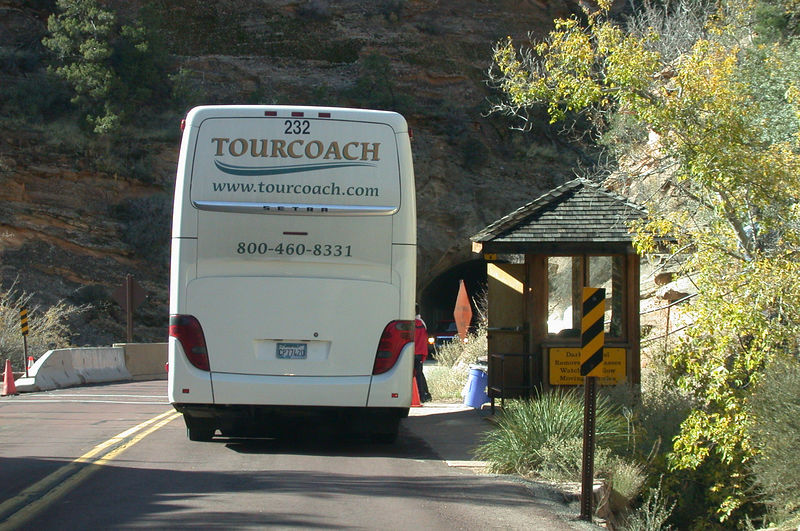 The bus is waiting for the tunnel to clear, because its<br /> height requires it to travel down the center of the road.