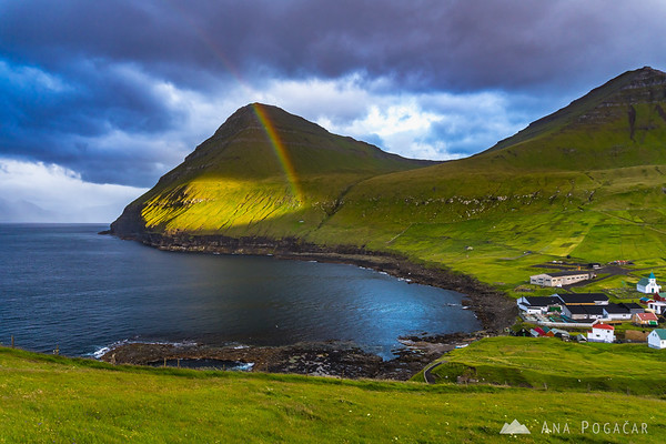 A rainbow appeared over Gjógv and the ocean for a brief moment on a cloudy afternoon