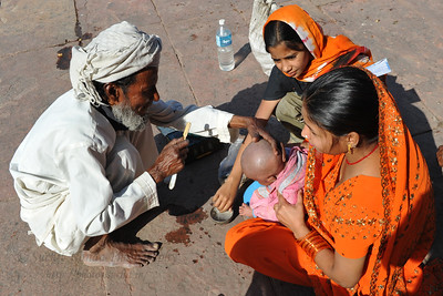 Young child getting a first hair cut in the form of a head-shaving in the courtyard of Jama Masjid at Fatehpur Sikri.  Fatehpur Sikri (Hindi: फतेहपुर सीकरी, Urdu: فتحپور سیکری) is a city and a municipal board in Agra district in the state of Uttar Pradesh, in North India. The historical city was constructed by Mughal Emperor Akbar beginning in 1570 and served as the empire's capital from 1571 until 1585. Though it took 15 years to build, it was abandoned after only 14 years of use because of shortage of water supply which was unable to sustain the growing population. The palace and mosque in Fatehpur Sikri are a tourist attraction and it is an UNESCO World Heritage Site which is about 40 km from the Taj Mahal, Agra. Uttar Pradesh state (UP), North India.