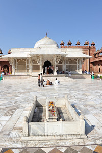 A white marble encased tomb within the Jama Masjid's courtyard is the Tomb of Salim Chisti - the sufi saint who lived as a recluse in the small town Sikri near Agra.  Fatehpur Sikri (Hindi: फतेहपुर सीकरी, Urdu: فتحپور سیکری) is a city and a municipal board in Agra district in the state of Uttar Pradesh, in North India. The historical city was constructed by Mughal Emperor Akbar beginning in 1570 and served as the empire's capital from 1571 until 1585. Though it took 15 years to build, it was abandoned after only 14 years of use because of shortage of water supply which was unable to sustain the growing population. The palace and mosque in Fatehpur Sikri are a tourist attraction and it is an UNESCO World Heritage Site which is about 40 km from the Taj Mahal, Agra. Uttar Pradesh state (UP), North India.