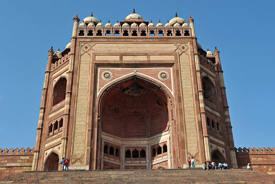 Buland Darwaza: One of the gateways to the Jama Masjid, is a stupendous piece of architecture. Fatehpur Sikri's main entrance is a lofty gate called Buland Darwaza. The Darwaza is 40 metres high and topped by pillars and chhatris. Buland Darwaza is considered to be the greatest architectural monument of Akbar's long reign. The Darwaza was built by Akbar in 1573 to commemorate the conquest of Gujarat.   Fatehpur Sikri (Hindi: फतेहपुर सीकरी, Urdu: فتحپور سیکری) is a city and a municipal board in Agra district in the state of Uttar Pradesh, in North India. The historical city was constructed by Mughal Emperor Akbar beginning in 1570 and served as the empire's capital from 1571 until 1585. Though it took 15 years to build, it was abandoned after only 14 years of use because of shortage of water supply which was unable to sustain the growing population. The palace and mosque in Fatehpur Sikri are a tourist attraction and it is an UNESCO World Heritage Site which is about 40 km from the Taj Mahal, Agra. Uttar Pradesh state (UP), North India.