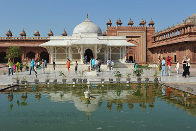 A white marble encased tomb with pond in front within the Jama Masjid's courtyard is the Tomb of Salim Chisti - the sufi saint who lived as a recluse in the small town Sikri near Agra.  Fatehpur Sikri (Hindi: फतेहपुर सीकरी, Urdu: فتحپور سیکری) is a city and a municipal board in Agra district in the state of Uttar Pradesh, in North India. The historical city was constructed by Mughal Emperor Akbar beginning in 1570 and served as the empire's capital from 1571 until 1585. Though it took 15 years to build, it was abandoned after only 14 years of use because of shortage of water supply which was unable to sustain the growing population. The palace and mosque in Fatehpur Sikri are a tourist attraction and it is an UNESCO World Heritage Site which is about 40 km from the Taj Mahal, Agra. Uttar Pradesh state (UP), North India.