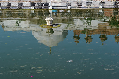 Reflections in the pond of the  marble encased tomb within the Jama Masjid's courtyard which is the Tomb of Salim Chisti - the sufi saint who lived as a recluse in the small town Sikri near Agra.  Fatehpur Sikri (Hindi: फतेहपुर सीकरी, Urdu: فتحپور سیکری) is a city and a municipal board in Agra district in the state of Uttar Pradesh, in North India. The historical city was constructed by Mughal Emperor Akbar beginning in 1570 and served as the empire's capital from 1571 until 1585. Though it took 15 years to build, it was abandoned after only 14 years of use because of shortage of water supply which was unable to sustain the growing population. The palace and mosque in Fatehpur Sikri are a tourist attraction and it is an UNESCO World Heritage Site which is about 40 km from the Taj Mahal, Agra. Uttar Pradesh state (UP), North India.