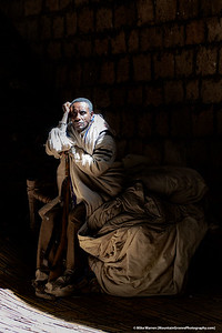 #7 – Outside Lalibela, Ethiopia.  A man, whom I believe to be a priest, sits in a ray of sunlight in one of the rock hewn churches of Lalibela, Ethiopia.  Notice his is holding a rifle, likely used to protect the church from wild animals.