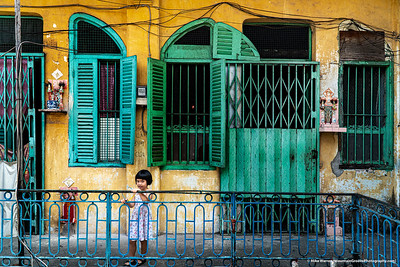 #27 – Ho Chi Minh City, Vietnam.   A young girl outside of her apartment home in the former Saigon.