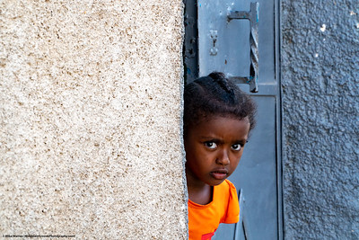 #5 – Harar, Ethiopia.   A young girl looks around the corner in one of the most holiest of Islamic cities.