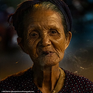 ##12A, 12B and 12C – Hoi An, Vietnam.  A very low light series of images of an elderly woman with a stub of a cigarette, wearing a conical hat.