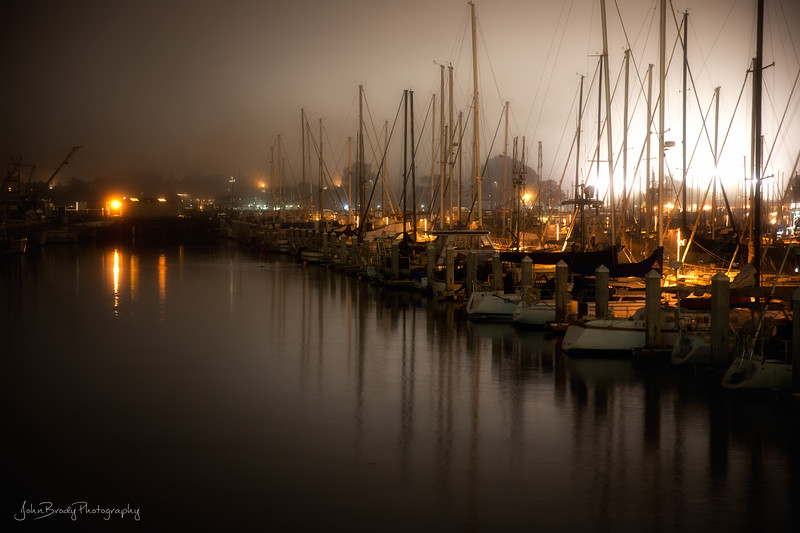 Cannery Row Marina in Monterey in  Midnight Fog  - The marina in Monterey depicted in the photo is an integral part of the waterfront described by Steinbeck in Cannery Row. I spent many nights in this type of drizzly fog during the two years I spent in Monterey, one of the more beautiful places I've lived. ----- Monterey Marina in Midnight Fog -  John Brody Photography - JohnBrody.com