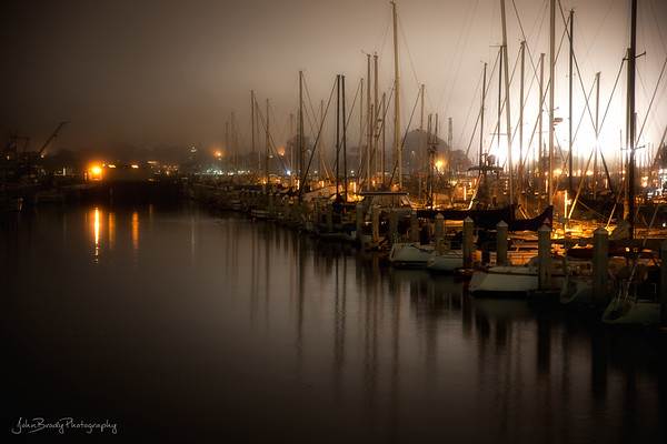 Cannery Row Marina in Monterey in  Midnight Fog  - The marina in Monterey depicted in the photo is an integral part of the waterfront described by Steinbeck in Cannery Row. I spent many nights in this type of drizzly fog during the two years I spent in Monterey, one of the more beautiful places I've lived. --- Monterey Marina in Midnight Fog -  John Brody Photography - JohnBrody.com