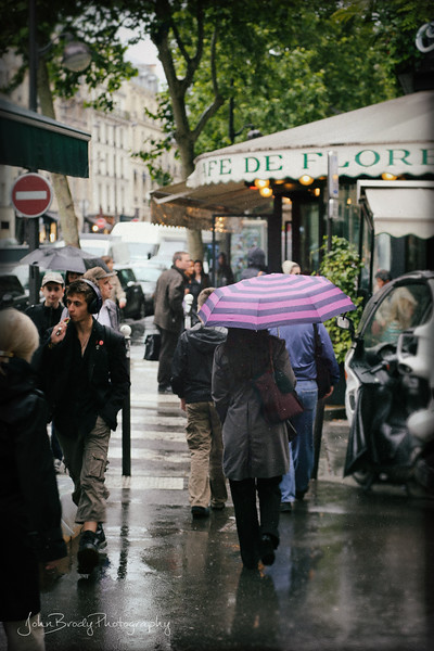 Foot Traffic on a Rainy Day in front of Cafe de Flore Paris, France - One of the top rated cafes in Paris and my personal favorite. The food is great, the waiters nice and the history is long and interesting; Hemmingway, Picasso and a host of others - Quite an atmosphere . Give it a Google for a motherload of  information and history :)    - JohnBrody.com / John Brody Photography