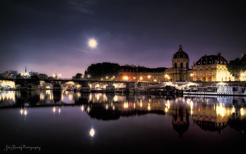 Moonrise Over Pont des Arts Paris,  *Pont des Arts Paris*  -  This bridge is never a boring place. During my last trip I saw so many types here - locals and travelers, the friendly and the pick-pockets, painters and musicians - every night was a different scene. On my last night there, I sat on the bridge and there were circles of friends enjoying wine, food and friendship. A motley gaggle of guys talked for a while, then pulled out instruments and broke into a blazing version of Sunshine of Your Love followed by a string of well played classics. They then bowed to the crowd and headed off into the night... I can't think of anywhere that would happen in Los Angeles. This footbridge is a very special place...    JohnBrody.com / John Brody Photography