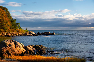 Fisherman on the Distant Rocks at Lobster Cove near Manchester-by-the-Sea Massachusetts,. This site was exploding with Fall Foliage when we visited  --- John Brody Photography - JohnBrody.com