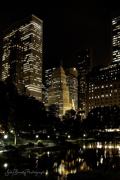 Skyline Reflection of Central Park NYC  by the Plaza and the well known NYC Apple Store. Photo taken from the Gapstow Bridge at the southernmost corner of Central Park near Wollman Ice Skating Rink, yes, the skating rink in almost every movie made in Central Park including Serendipity, Limitless, and Love Story to name a few :)   -   JohnBrody.com / John Brody Photography