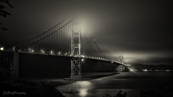 """San Francisco Golden Gate Bridge Long Exposure Photography ---   I never quite understood the old quote often attributed to Mark Twain, """"The coldest winter I ever spent was a summer in San Francisco,"""" until the night I took this photo...   A few hours after sunset on a warmish mid-July night, I showed up at the recommended hillside overlooking the bridge with my camera gear and tripod, dressed in a toasty flannel shirt that was way too warm for the night. In fact, after the little hike to the hillside, I was flat out hot, uncomfortably so. I mumble-cursed Mr. Twain for obviously writing for effect instead of accuracy.  Three hours later I was begging his forgiveness. The temperature had dropped impossibly while the sea breeze had turned into sea blasts that brought an icy chill at unbelievable force. It literally flapped my shirt so hard that it unbuttoned itself and was snapping like a flag at 90 degrees. The shirt issue became a non-issue because I was hanging on to my not-inexpensive camera gear with both hands and still lost a lens cap and a few lens cushions that got sucked out of my camera bag - gone. The tripod stood no chance and was being blown over even with fully spread legs and a 20+ pound camera bag hanging on it for stabilizing weight - It didn't matter. The whole rig would blow over and head for the ground the second I let go of it.  Another battered photographer and I teamed up to deal with the mess. We had the brilliant idea of lashing the tripods to a sturdy post we found but felt fools for thinking there was any twine or cord for miles... His sweet petite girlfriend overheard us, reached in her purse and pulled out a 50 foot spool of yellow and black twisty 1/4 inch nylon rope, still on the spool. He and I looked at each other with puzzled amazement, but a heavy blast of frigid air made us forget about wondering why she had 50 feet of rope in her purse and what the hell else might be in there...  Well, I'll try to wrap up this one sentence descrip"""