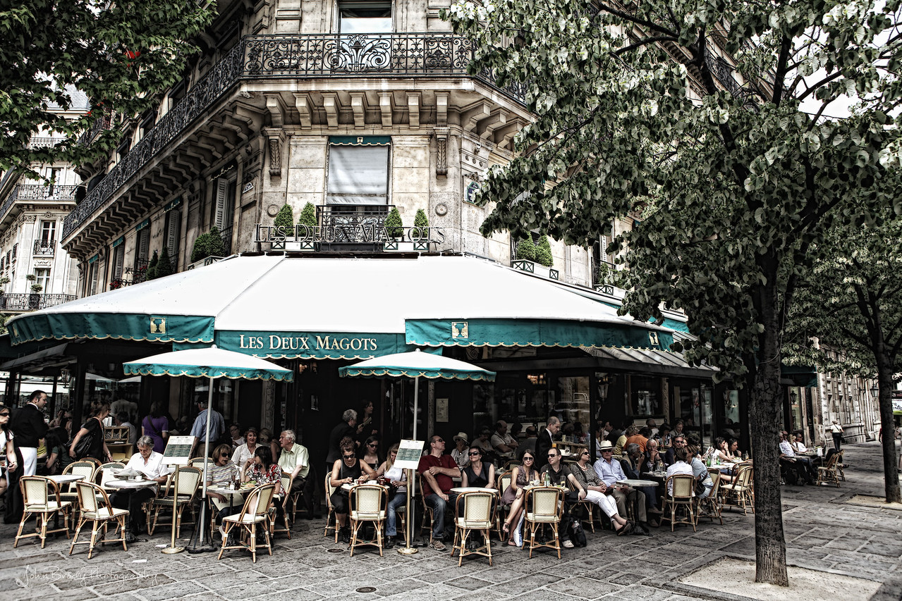 Cafe Les Deux Magots - This famous cafe on the Left Bank of the Seine, Les Deux Magots is popular with both tourists and Parisians, It has a long history as a meeting place for famous writers and philosophers. Deux Magots was once a favorite spot for existentialist writers Jean-Paul Sartre and Simone de Bouvoir, and a favorite of Hemmingway and Picasso where he reportedly created cubism -  Image was taken with Canon 5D Mark III and a Series II 24-70 L Series lens  - JohnBrody.blogspot..com  / JohnBrody.com / John Brody Photography / JohnBrodyPhotography.com