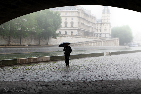 A Little Rain Gives Solitude To A Stroller - Pont Neuf Bridge over the River Seine in Paris, an area usually swarming with people - The Umbrella Man - JohnBrody.com / John Brody Photography