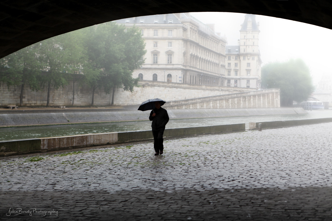 A Little Rain Gives Solitude To A Stroller - He said the rain lets him enjoy peaceful strolls along Pont Neuf Bridge and the River Seine in Paris, an area usually swarming with people - AKA The Umbrella Man - John Brody Photography / JohnBrodyPhotography.com / JohnBrody.com