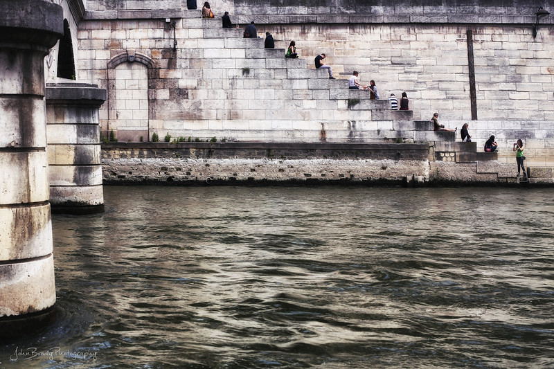 Locals Resting on Seine River Wall Near the Cathedral At Notre Dame in Paris . I was shooting something completely different when this scene just appeared as the lunchtime crowd appeared from the shops up above the river. Looking like an old Willy Ronis ( or Robert Doisneau?) shot I remembered, I had to catch the moment. Ten minutes later it was all gone.   JohnBrody.com / John Brody Photography