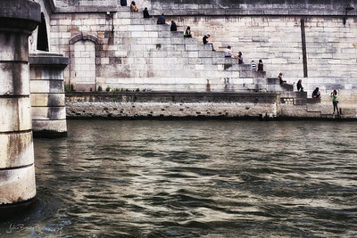 Locals Resting on Seine River Wall Near the Cathedral At Notre Dame in Paris - JohnBrody.com / John Brody Photography