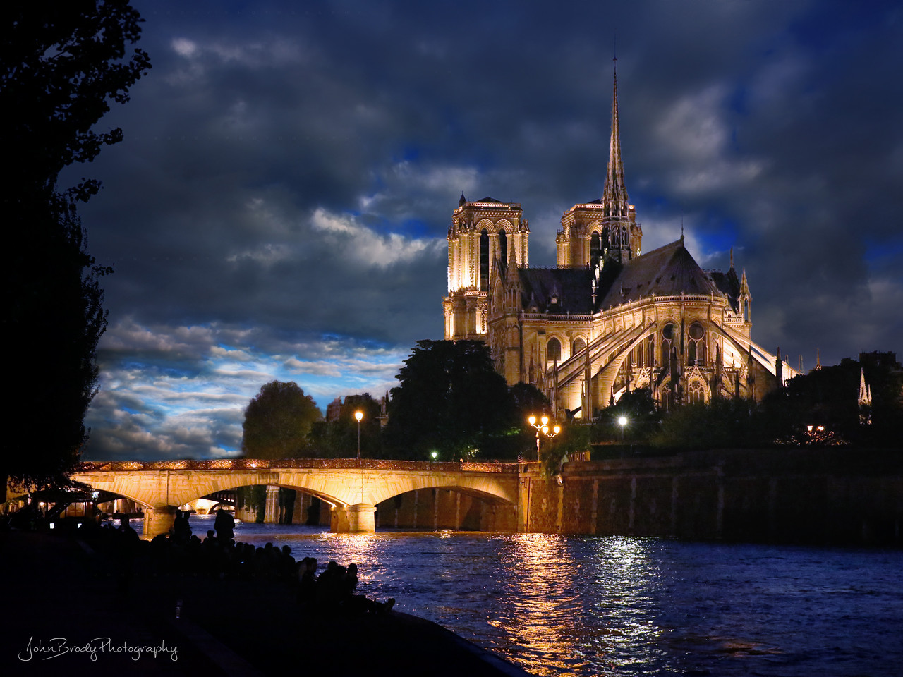 Notre Dame Cathedral at Sunset - Paris locals gather at dusk in circles of friends on the Seine riverbank across from the Cathedral. I post this as I follow the efforts of the French to rebuild this wonderful architectural masterpiece. - John Brody Photography / JohnBrodyPhotography.com / JohnBrody.com