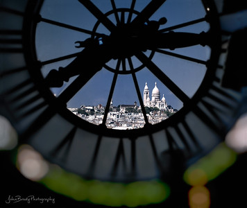 Sacre Coeur Cathedral in Montmartre Paris photographed through the d'Orsay Museum Clock