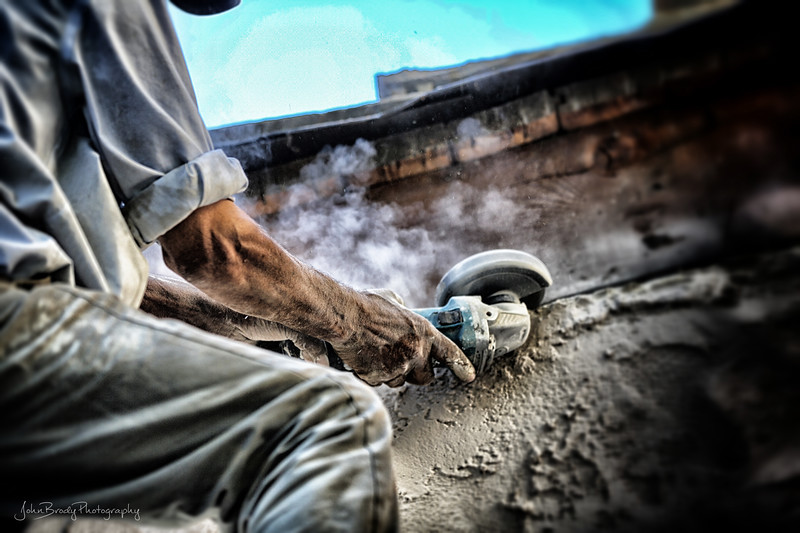 A gritty image out of my normal travel genre, I couldn't pass it up. A good tradesman making a home water tight. The lighting and subject made it a a must shoot... - JohnBrody.com / John Brody Photography