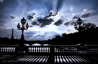 A spectacular day in Paris!  I'm on Pont Alexandre III looking at the clouds and the Eiffel Tower. Loved the shadows cast off by the clouds. The low sun made the the earth turn into a expansive silhouette. Only he water and the sky got the benefit of the light, leaving trailing shadows from th clouds and on the bridge - JohnBrody.com / John Brody Photography