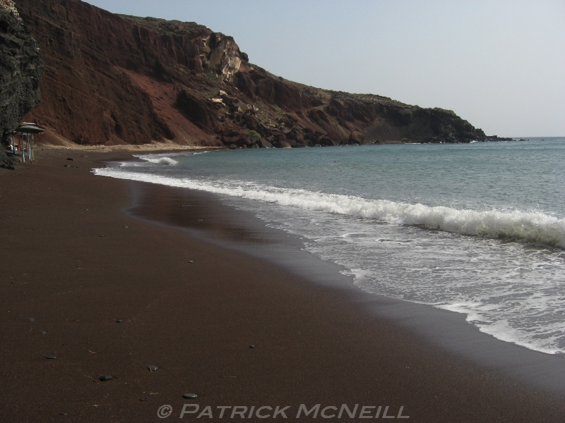 Red Beach on Santorini, Greece. A beautiful, isolated beach with sand that was a colour I'd never seen before. This photo has wet sand so it looks really dark. No people here and an excellent beach overall.