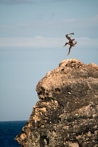Native man jumps on cliff during traditional dance