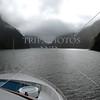 Ship cruising along Milford Sound in Fiordland National Park, New Zealand.