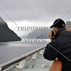 Cruise passenger taking photos of the scenic view along the Breaksea Sound in Fiordland National Park, New Zealand.