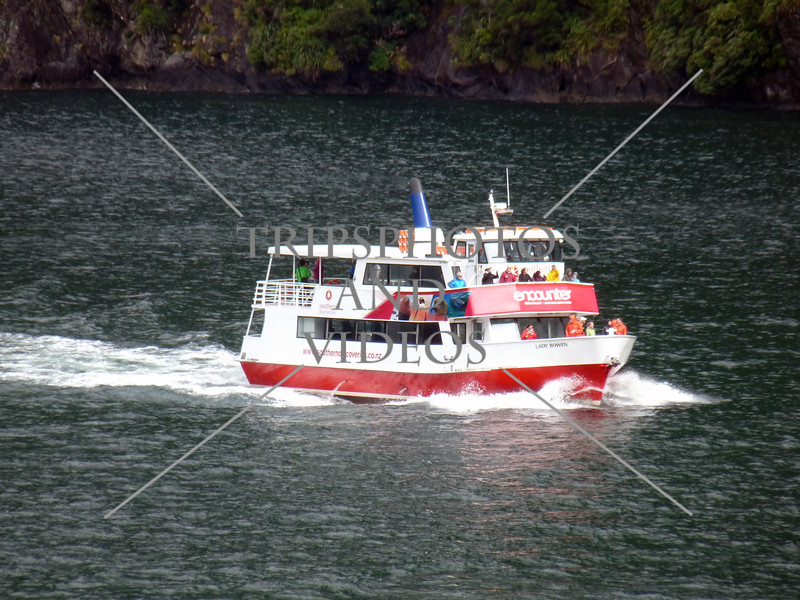 Tour boat cruising along Milford Sound in Fiordland National Park, New Zealand.