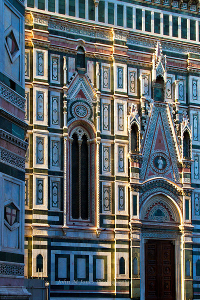 Late evening sunlight emphasizes  the relief on the facade of the Santa Maria del Fiore or the Duomo, Florence, Firenze, Italy