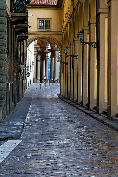 Jogger under Vasari's Arno River facade at the Uffizi