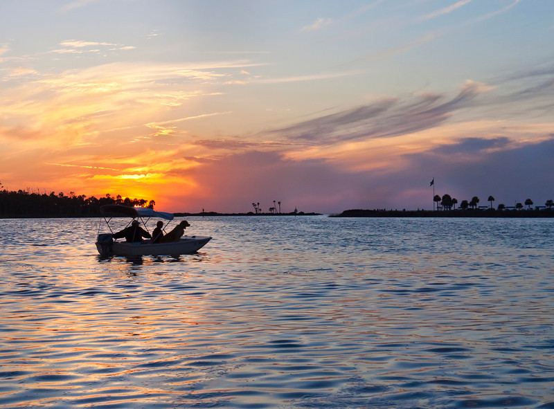 People in a boat setting out to fish at sunset with their dog in Florida