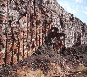 1/14/07 - Molten slag from the processing of the ore was deposited behind this barricade of corrugated steel, which has since rusted away for the most part, leaving the pattern of the corrugations cast into the mountain of waste.