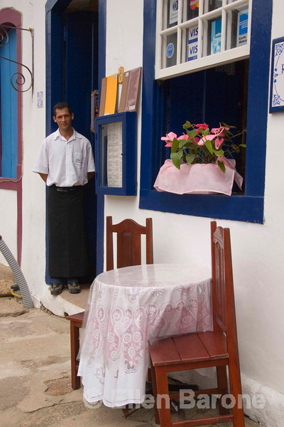 A friendly waiter passes time in a doorway at Gina Restaurant & Pizzaria in colonial Parati, a UNESCO World Heritage community, Brasil. ©2007 Ellen Barone.