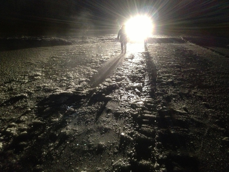 Trip to Fort Albany -- checking out a creek crossing. Looking towards Albalina Metatawabin's vehicle with lights on. Thin top ice over water on top of ice. Probably from recent flooding. Creek on way north. Ruts from previous vehicle. DEnise Metatawabin walking towards camera.