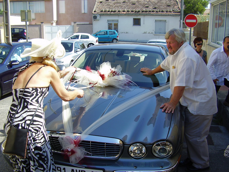 Nella seeing to the decorations on the wedding car while Jean-Pierre looks on.